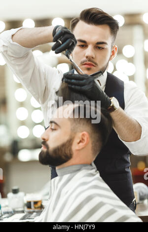 Barber doing haircuts for client - Stock Photo