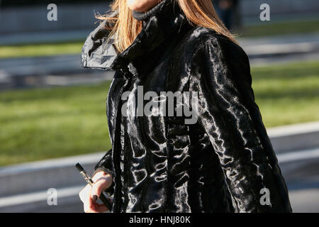 Woman with black shiny fur coat before Giorgio Armani fashion show, Milan Fashion Week street style on January 17, - Stock Photo