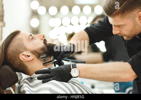 Barber making beard form for man - Stock Photo