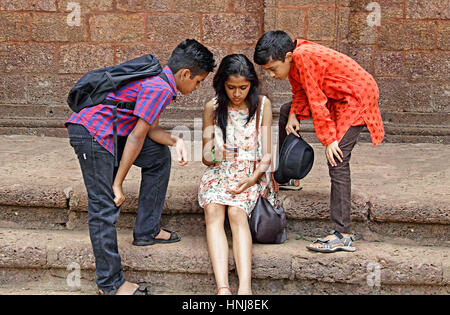 Young girl sitting on steps work on smartphone while her teenage friends keenly watch - Stock Photo