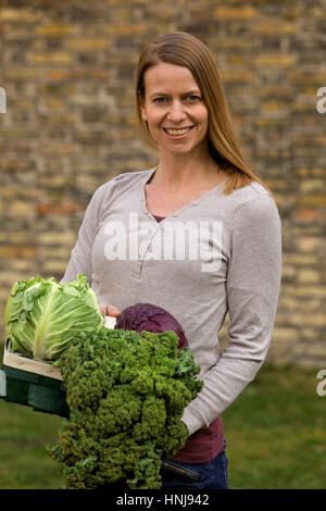 woman with winter vegetables in garden - Stock Photo