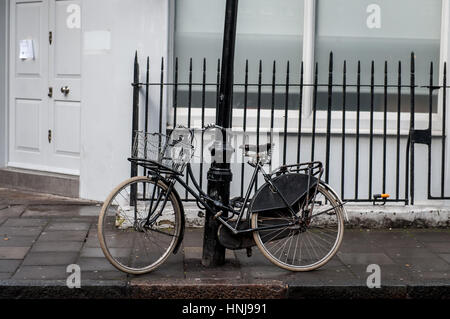 An old fashioned bike parked on the pavement in London's Fitzrovia - Stock Photo