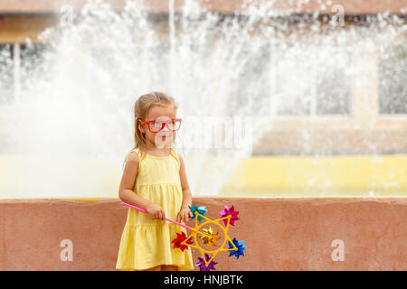 Cute little girl holding a pinwheel in hand. A walk in the summer park near the city fountain. Summer vacation. - Stock Photo