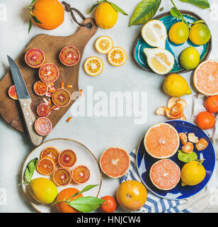 Natural fresh citrus fruits on wooden rustic board, colorful ceramic plates over grey marble table background, top - Stock Photo
