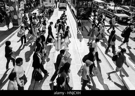 Hong Kong, Hong Kong - April 17 2015: People cross a street in Hong Kong island central district. Captured in black - Stock Photo