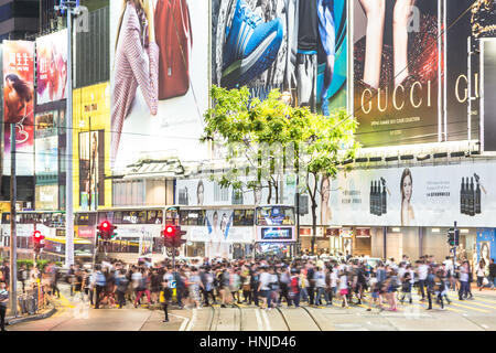 Hong Kong, Hong Kong - April 20 2015: People, capture with blurred motion, cross the street in the busy Causeway - Stock Photo