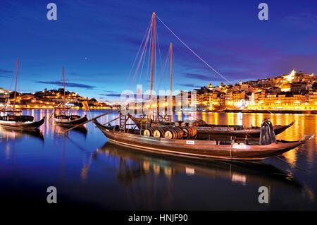 Romantic nocturnal view of Oporto with Rabelo boats anchoring in Vila Nova de Gaia - Stock Photo