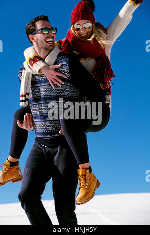 Couple playing in snow. Man giving woman piggyback ride on winter vacation. - Stock Photo