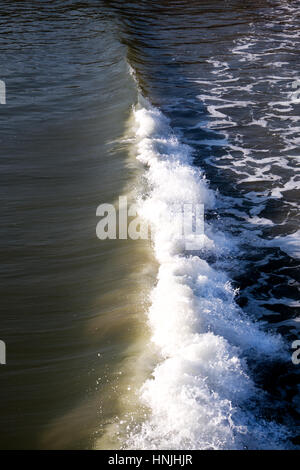 small wave breaking photographed from above, breaking wave running in a line through centre of the image, sea on - Stock Photo