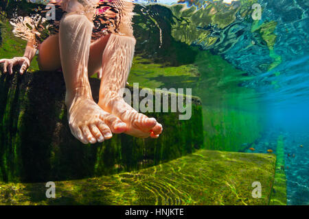 Happy person have fun at poolside edge. Funny under water photo of baby bare feet in natural pool. Family lifestyle. - Stock Photo