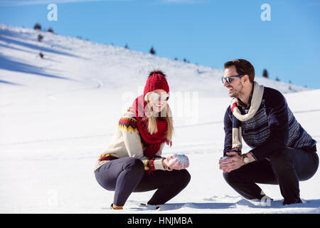 Snowball fight. Winter couple having fun playing in snow outdoors. Young joyful happy multi-racial couple. - Stock Photo