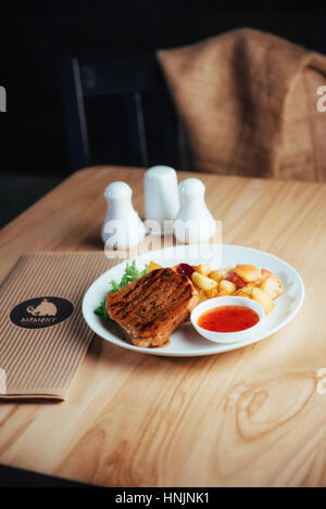 Steak with crispy golden fries and tomato spicy sauce - Stock Photo