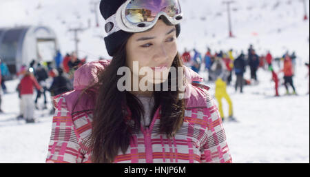 Portrait of pretty young woman on skiing holiday with people skiers in background - Stock Photo