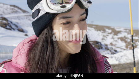 Portrait of smiling young woman on skiing holiday with goggles on forehead and mountains in background - Stock Photo