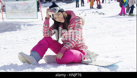 Happy young woman in pink snowsuit sat on ground with snowboard during skiing holiday - Stock Photo
