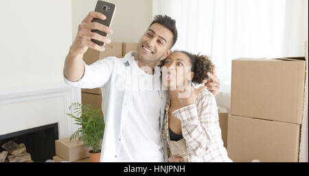 Fun young couple taking their selfie on a mobile phone pulling faces as they pose in front of packing boxes in their - Stock Photo