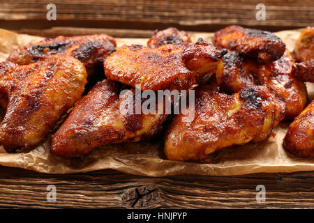 Chicken wings baked in a pan on wooden background - Stock Photo
