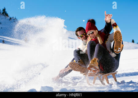 Young Couple Sledding And Enjoying On Sunny Winter Day - Stock Photo
