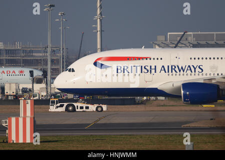 A British Airways Airbus A380 being pulled by a Douglas TBL-600 tug at London Heathrow Airport - Stock Photo