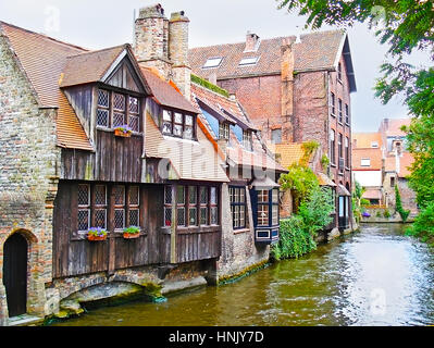 The row of the old brick mansions with wooden balconies, standing on Den Dijver Canal, at Bonifacius Bridge, Bruges, - Stock Photo
