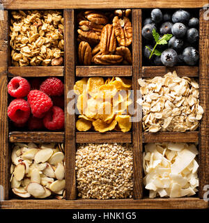 Breakfast foods, oats, cereals and fruit in a wooden box overhead shot - Stock Photo