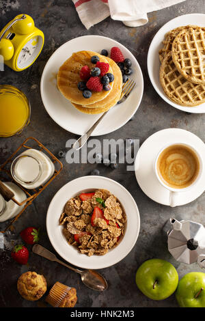 Healthy breakfast on the table with cereals, fruit, pancakes and waffles overhead shot - Stock Photo