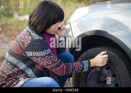 Woman changing a wheel on a car on the empty road, Selective focus and small depth of field - Stock Photo