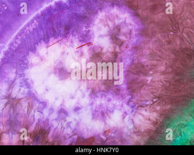 textile background - stylized violet heart hand painted on silk batik in nodular technique - Stock Photo