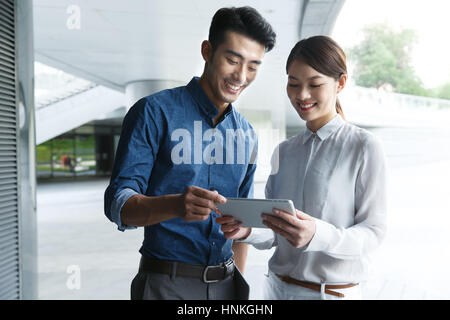 Business young men and women use tablet PCs - Stock Photo