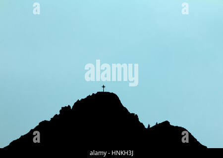 Black silhouette of mountain peak with summit cross. Blue background. - Stock Photo