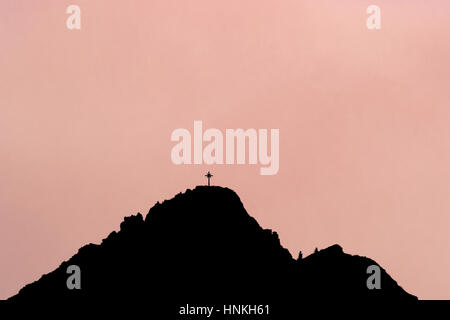 Black silhouette of mountain peak with summit cross. Rose background. - Stock Photo