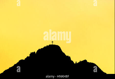 Black silhouette of mountain peak with summit cross. Yellow background. - Stock Photo