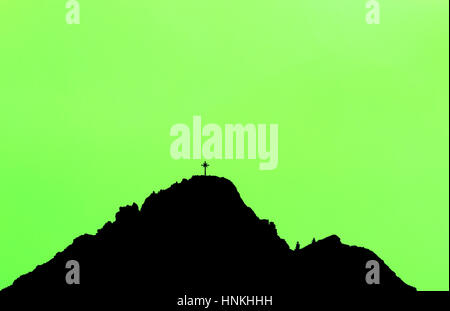 Black silhouette of mountain peak with summit cross. Green background. - Stock Photo