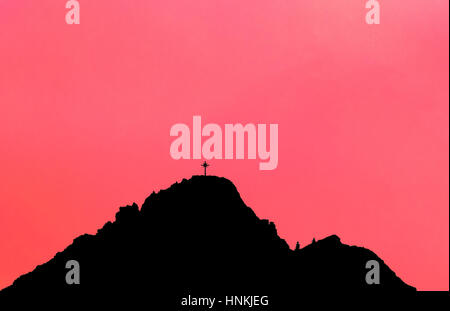Black silhouette of mountain peak with summit cross. Pink background. - Stock Photo
