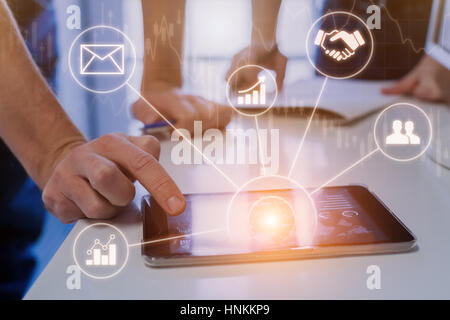 Business people during meeting in modern office using tablet computer for data and stock market analytics, icons - Stock Photo