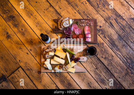 Charcuterie and cheese platters with craft beer and red wine. - Stock Photo