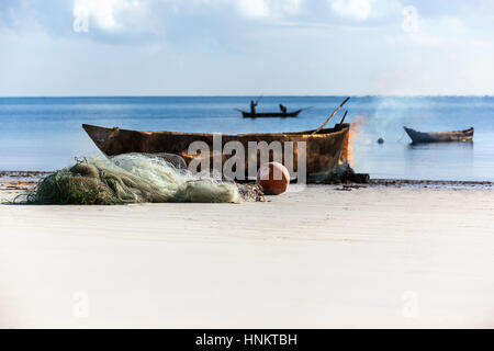 Coast of Mombasa. The old boat and fishing instruments on the beach with fishermen on boat in the water on background. - Stock Photo