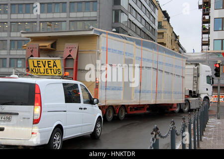 HELSINKI, FINLAND - JANUARY 16, 2017: Escort vehicle assists wide load oversize transport of Temporent prefabricated - Stock Photo