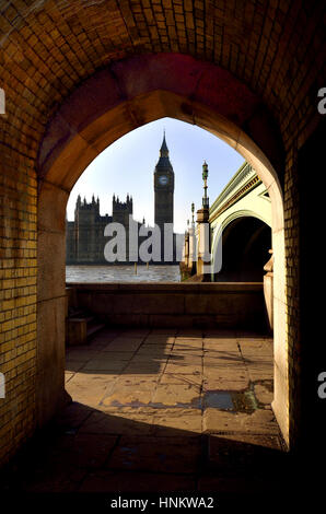 London, England, UK. Big Ben and the Houses of Parliament seen through an arch under Westminster Bridge - Stock Photo