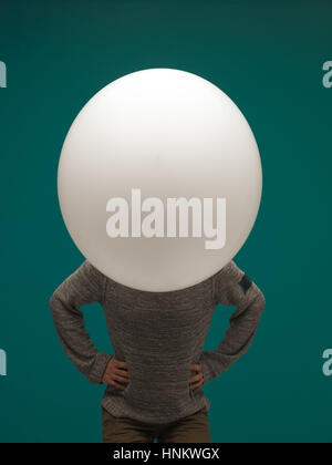 funny young man huge balloon on blue background. head - balloon - Stock Photo