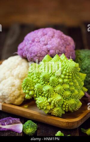 Fresh organic white and purple cauliflower, broccoli, romanesco in wooden bowl - Stock Photo