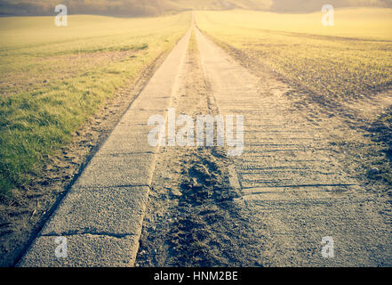 A long straight road leading to a vanishing point - Stock Photo