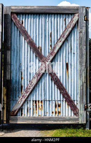 Old barn wooden bracing frame with zinc sheet door. - Stock Photo