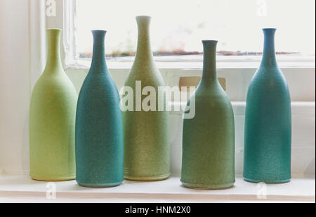 Green and Turquoise bottles on a windowsill - Stock Photo