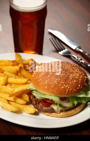 Photo of a burger with fries and a cold beer served at a Pub. - Stock Photo