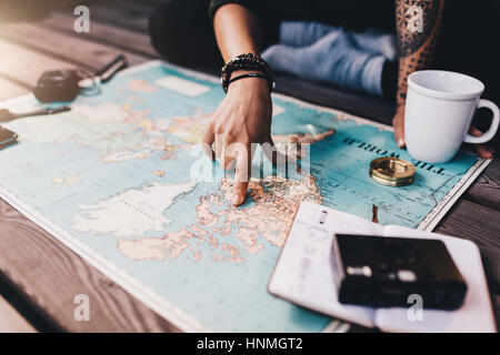 Tourist planning vacation with the help of world map with other travel accessories around. Young woman pointing - Stock Photo