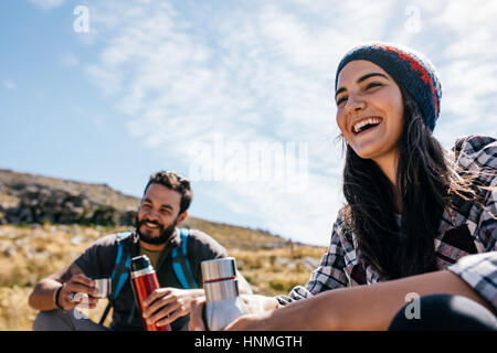 Smiling young woman taking a break during hiking. Cheerful hikers having rest on field - Stock Photo