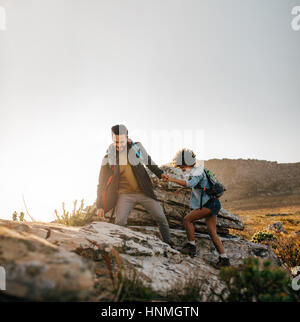 Young couple hiking help each other in mountains. Young male hiker helping female friend while trekking in mountain. - Stock Photo