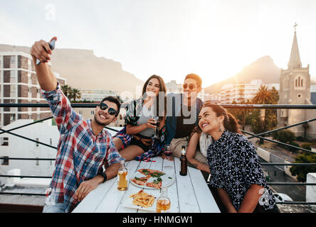 Group of friends having a party on the rooftop making a selfie. Happy young people taking self portrait during party. - Stock Photo