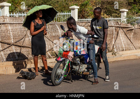 Two Young Men On A Motorcycle Stop To Talk To An Attractive Female In The Street, Arba Minch, Ethiopia - Stock Photo